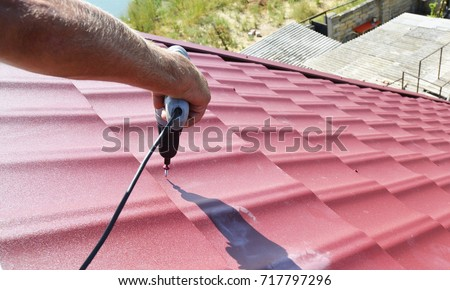 Roofing contractor installing metal roof tile for roof repair after hurricane damage. #717797296