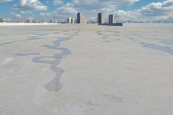 Roofing membrane after the rain, against the backdrop of the city. Water on the roof of the membrane.