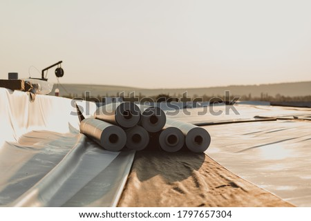 Roofing PVC membrane in rolls placed on the roof of a hall.Rubber membrane ready to be mounted. Stock photo ©