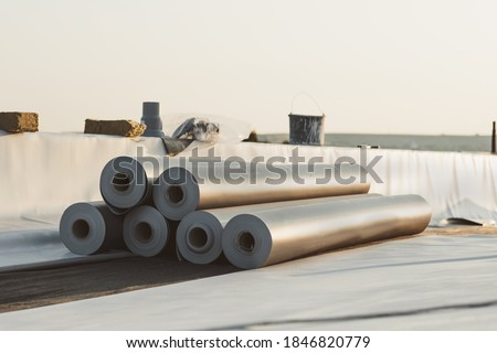 Photo of  Roofing PVC membrane in rolls placed on the roof of a hall.Rubber membrane ready to be mounted.
