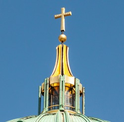Rooftop cupola with large golden christian cross on top of Berlin Dome