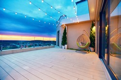 rooftop deck patio area with hanging chair and lights on a sunset