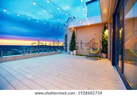 rooftop deck patio area with hanging chair and lights on a sunset Stock photo ©