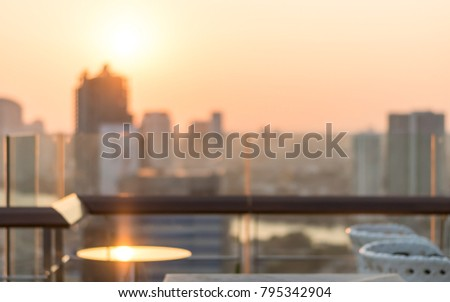 Rooftop party blur city view background from hotel balcony toward blurry restaurant bar dining table during happy hour romantic dinner with golden light evening sunset and sun flare