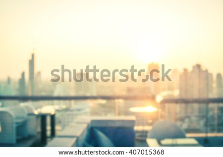 Rooftop party concept: Blurred dining table restaurant with beautiful city view at twilight scene background