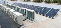 rooftop solar panels and air conditioning on top of an apartment block