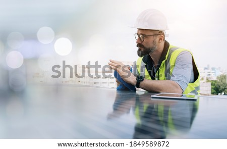 Rooftop solar power plant engineers sitting and examining photovoltaic panels. Concept of alternative energy and its service. Electrical and instrument technician use laptop to maintenance electric