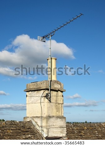 Rooftop TV Antenna, Chimney and Tiles Set against a Blue Sky