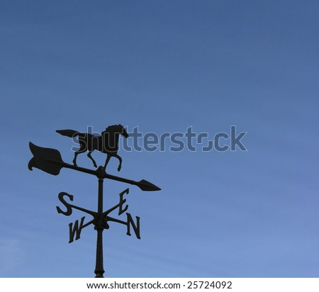 Rooftop weather vane against a clear blue sky.