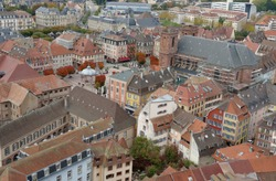 Rooftops of the old city of Belfort. Aerial view of the historic houses and buildings arranged densely to each other. View from the citadel or fortress surrounding the city.