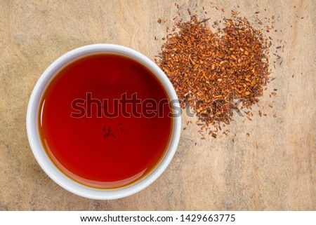 rooibos red tea  -  a white cup of a hot drink and loose leaves, tea made from the South African red bush, naturally caffeine free