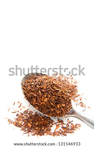 Rooibos tea  with spoon close up isolated on white background.