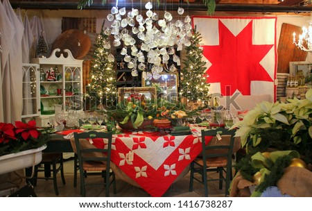 Room decorated for Christmas with huge red and white quilts, a chandelier made from old cut glass punch cups, fruit oranges, greenery, poinsettias and antiques.