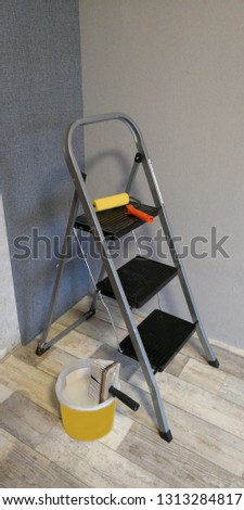 Room during repair-wallpapering: stepladder, standing in the corner, with a roller lying on it to smooth the wallpapers, a bucket of glue and a brush, with gray wallpaper on the walls, selective focus #1313284817