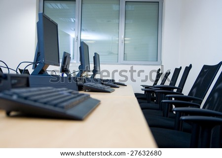 Room equipped with black computers and chairs.