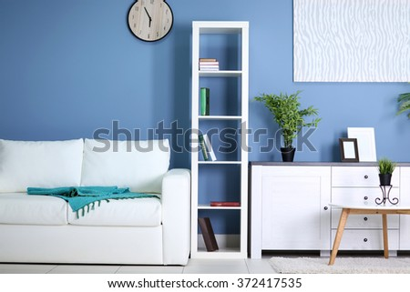 Room interior with commode, bookcase, table and sofa on blue wall background #372417535