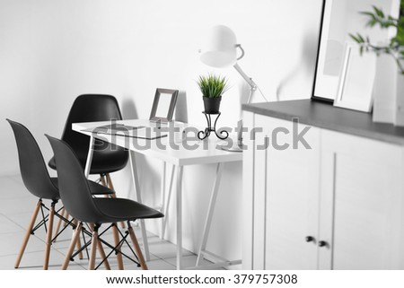 Room interior with commode, frames, chairs and table on white wall background #379757308