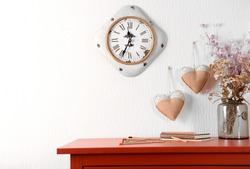 Room interior with red wooden commode, flowers and clock on light wall background