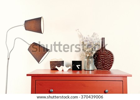 Room interior with red wooden commode, lamp and vase on light wall background #370439006