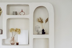 Room interior with wall design, decor at niche shelf. Modern home decoration, indoors apartment style in white. Vintage archs, exotic space of living room. Natural decorative elements.
