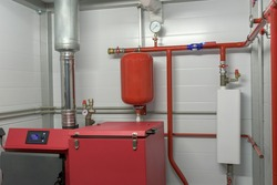 Room is a home boiler room. Stove, fuel box, metal pipe. Water supply system with pressure gauges. Concept of autonomous heating of the building.