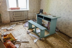 Room of an old abandoned building filled with trash on the floor and retro wooden simple painted desk.