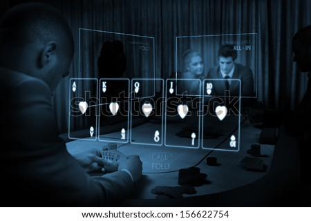 Room of people gambling on table with holographic card display in blue light in dark room