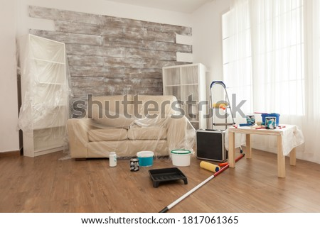 Room ready for renovation covered with plastic wrap. Plastic sheet. Home during renovation, decoration and painting. Interior apartment improvement maintenance. Roller, ladder for house repair