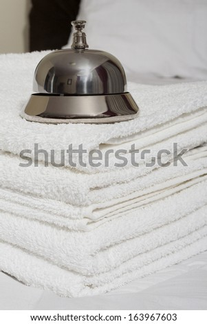 Room service bell and towels on bed