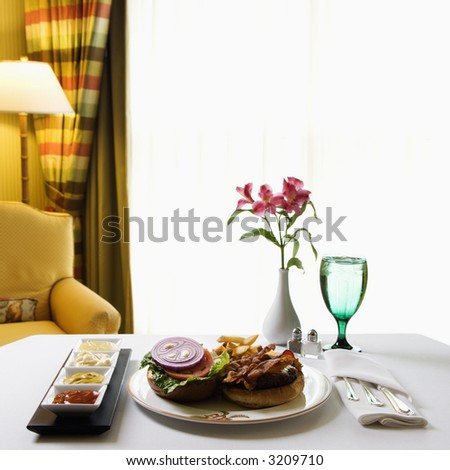 Room service cheeseburger meal with flowers and condiments.