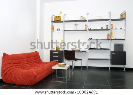room with a sofa and a modern wardrobe for books and articles