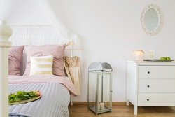 Room with bed, dresser, decorative lantern and mirror
