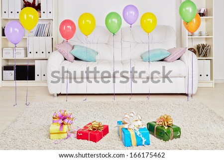 Room with big sofa, gift boxes on the floor and birthday air balloons hanging in the air