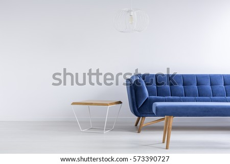Room with blue sofa, bench, metal and wood table
