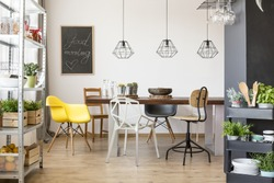 Room with communal table, chairs, industrial regale and cart