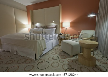 Room with king-size bed bedside table armchair  lamps and curtain