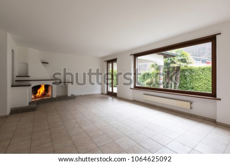 Room with large windows and lit fireplace on a cold winter day. Nobody inside #1064625092