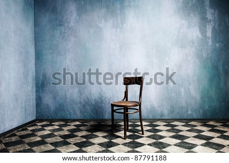 room with old blue walls and tiled floor with wooden chair in the middle