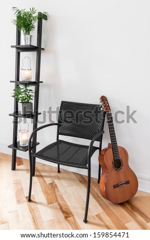 Room with simple black furniture, plants and classical guitar.
