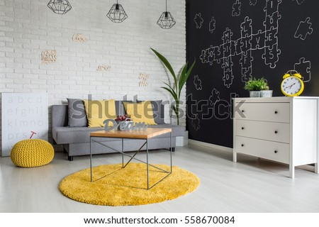 Room with sofa, dresser, blackboard wall and yellow details #558670084