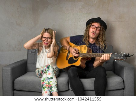 Roommate playing loud music on guitar disturbing and annoying friend