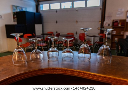 Rooms for rent in community arts center. A close-up view of empty wineglasses stood upside down on a counter ready for use during a club gathering in a recreational building. #1464824210