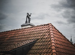 Rooster on the roof with red tiles and cloudy weather, Prague, Czech Republic