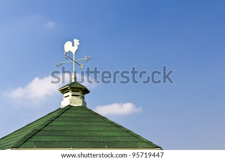 Rooster weather vane on roof and blue sky background