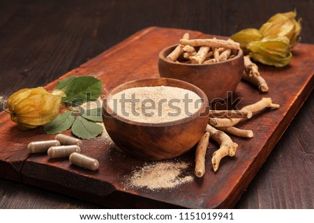 Roots and powder of Ashwagandha also known as Indian ginseng on wooden background. Hair loss, anti cancer, testosteron and depression benefits.