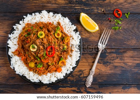 Ropa Vieja, Cuban national dish, stewed beef with wine and tomatoes on a black plate with a boiled rice. Wooden rustic table, top view.