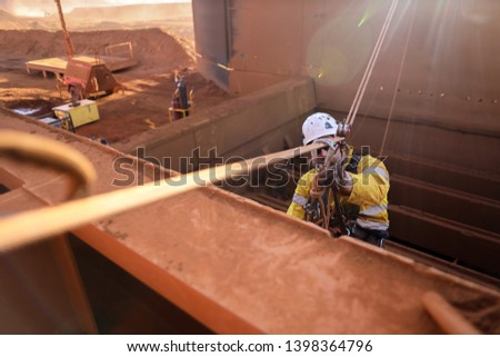 Rope access abseiler welder wearing safety full protection helmet working at height on tension line anchor point connecting with pulley double checking on locking Karabiner before descending down