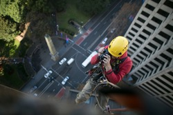 Rope access engineer inspector rappelling, working at height, inspection taking pictures of building structure creak, leaking for further report construction  Elisabeth St, Sydney CBD Australia