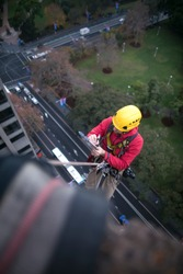 Rope access engineer worker rappelling, working at height, inspection writing notice of structure creak, leaking for further report at construction building site   Sydney City, Australia