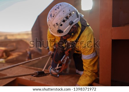 Rope access industry abseiler welder wearing safety full protection helmet while working at height construction site, Sydney, Australia   #1398371972